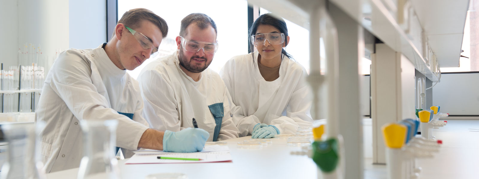 two male scientists and a female scientist work in a lab with lab coats and safety goggles