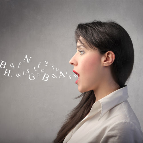 a side profile of a woman who stands with her mouth open as words fly out
