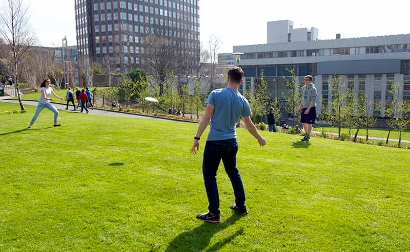 Students playing frisbee in Rottenrow Gardens