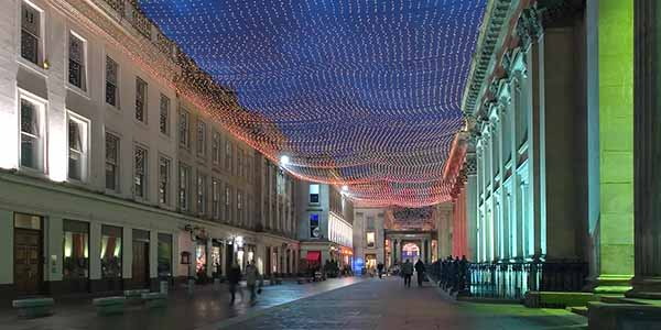 Royal Exchange Square at night, lit up in lights