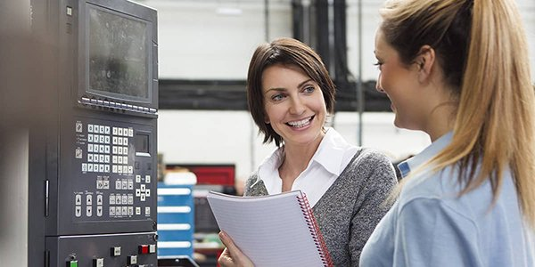 Factory executive talking to a female apprentice employee