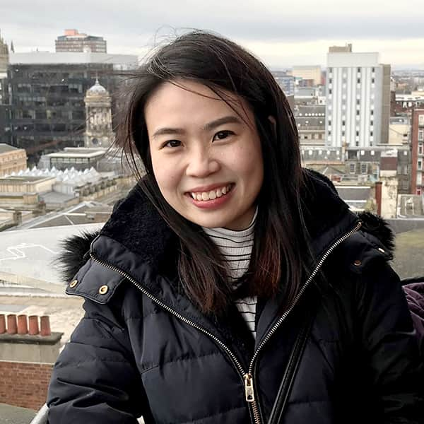 Kylie Ang She Tou standing at the top of the The Lighthouse, Glasgow, with Glasgow skyline in the backdrop