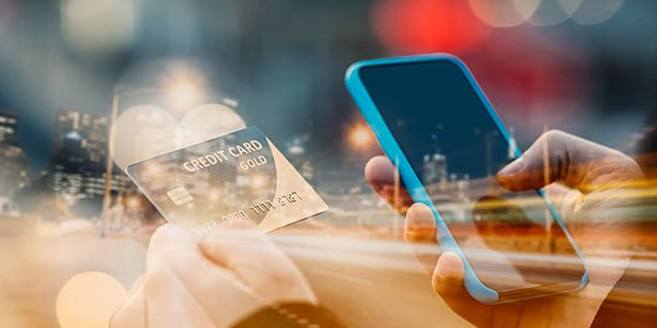 A person holding a mobile phone and credit card