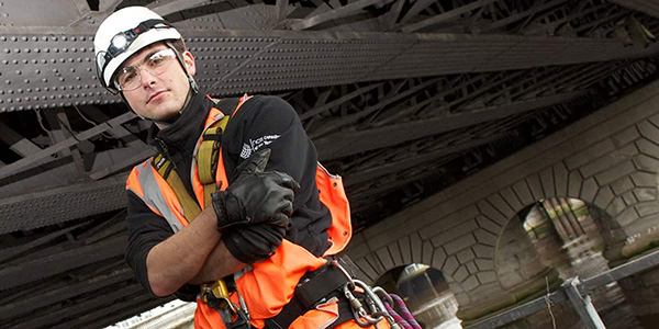 Safety worker stands in hard hat,600x300