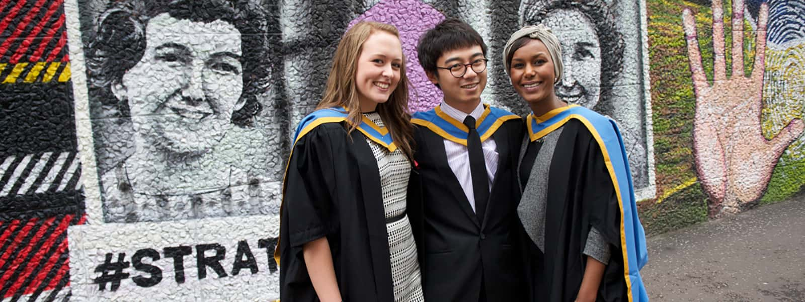 Three new graduates pose outside Graham Hills building, George Street