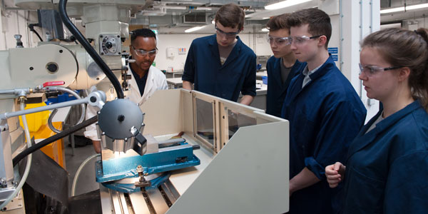 a lecturer teachers engineering students how to use a large machine