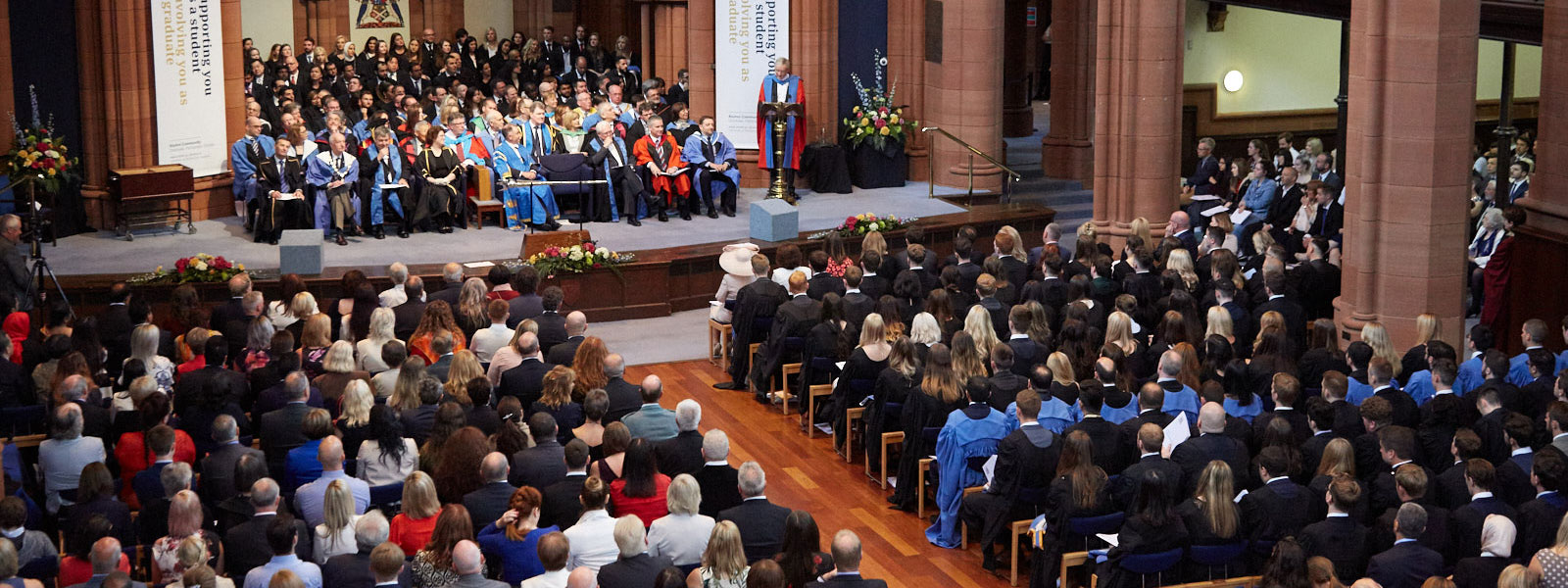 a birds-eye view of guests and graduates sitting in the Barony Hall during a graduation ceremony