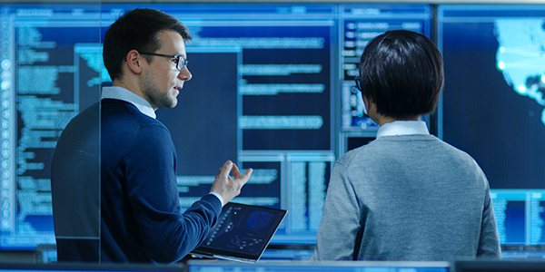 Two people having a discussion in a systems control room