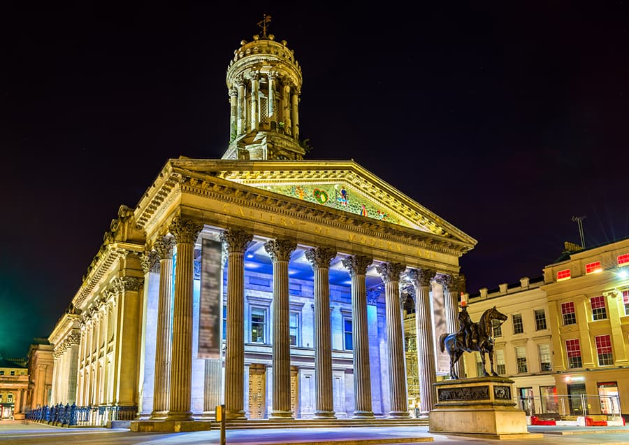Gallery of Modern Art lit up at night, with the Duke of Wellington statue standing in front
