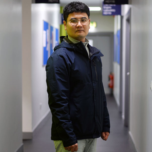 Sung il standing in the Henry Dyer corridor smiling at the camera