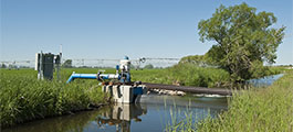 A pump in a stream provides water to a pivot irrigation system that waters a field of crops.