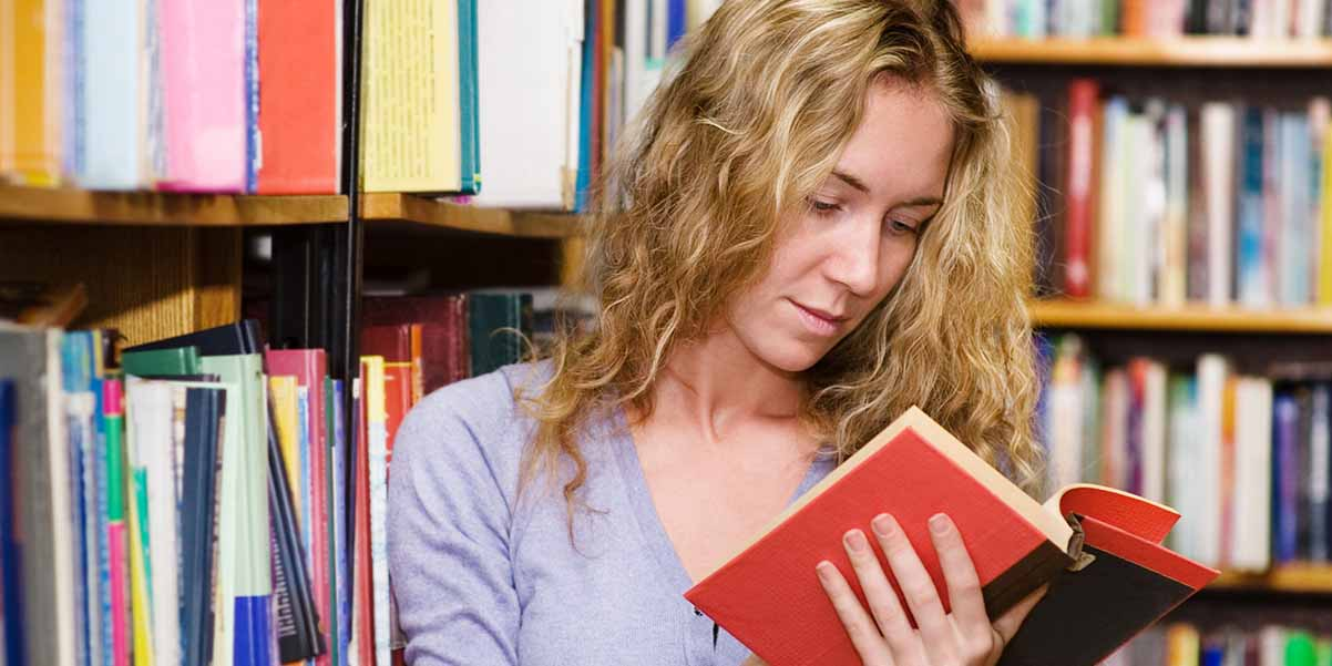 Student in library with books.