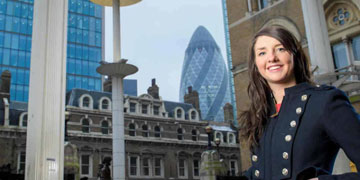 Female student in London, Gherkin building in background.