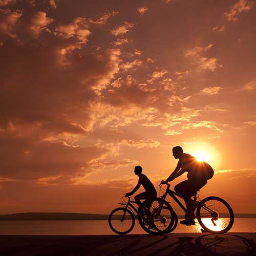 Couple cycling at sunset