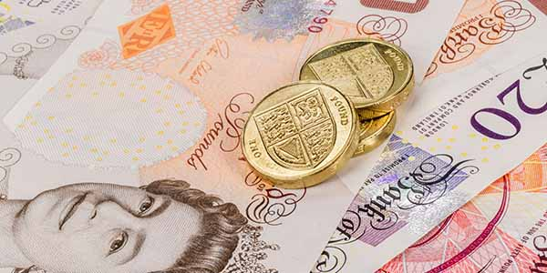 UK currency - pound coins sitting on top of bank notes