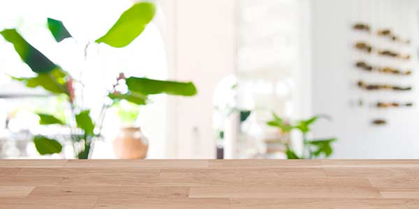 Wooden table top on blurred abstract interior with plants in the background.