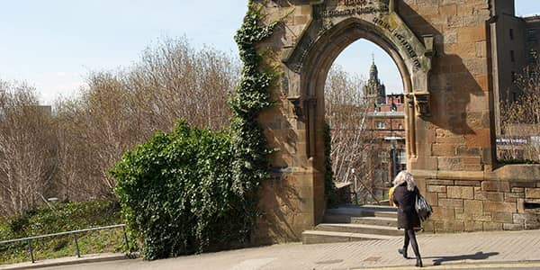 Student walking past archway at Rottenrow Gardens