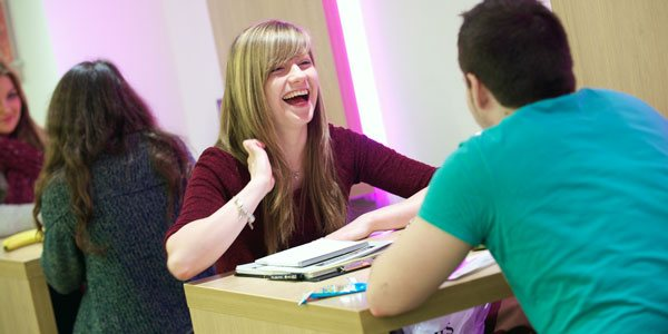 a female student laughs with another student over lunch in one of the campus cafes
