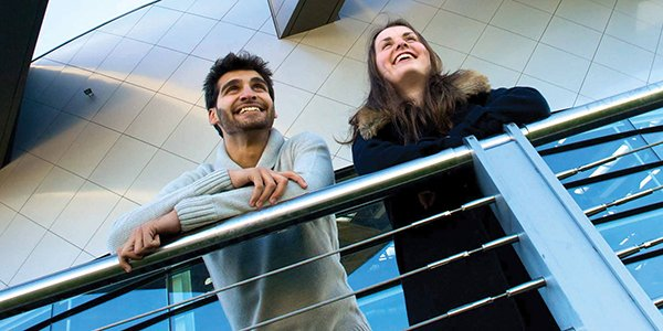 Male and female student stand on balcony on campus, 600x300