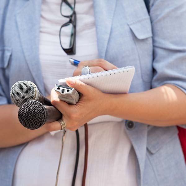 Journalist holds microphones and Dictaphone while taking notes/