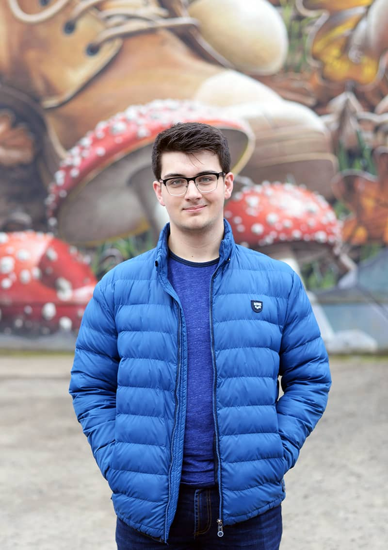 Jack McMullan, LLB (Hons) in English Law student, standing in front of street art on Ingram Street