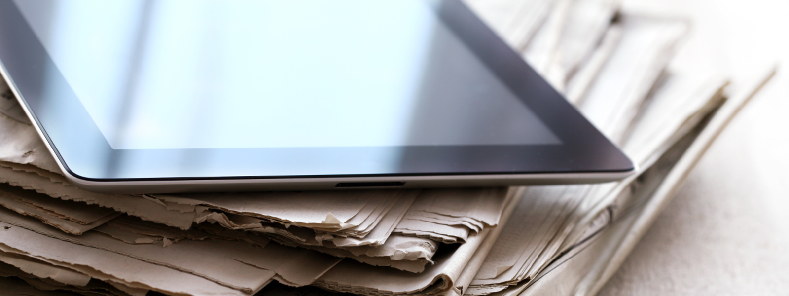 Bundle of newspaper and a tablet computer