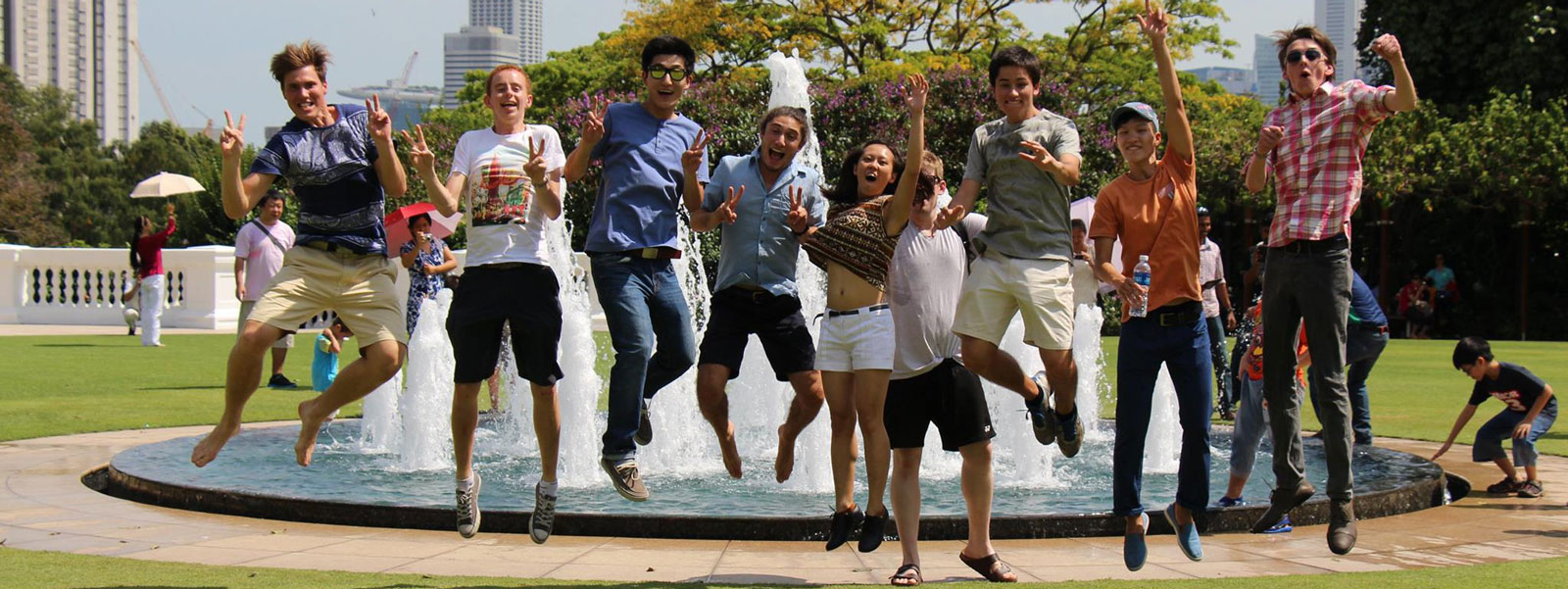 students jumping in front of fountain
