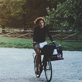 Woman on a bike ride through the park.