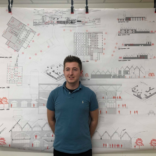 Student in front of architectural drawings