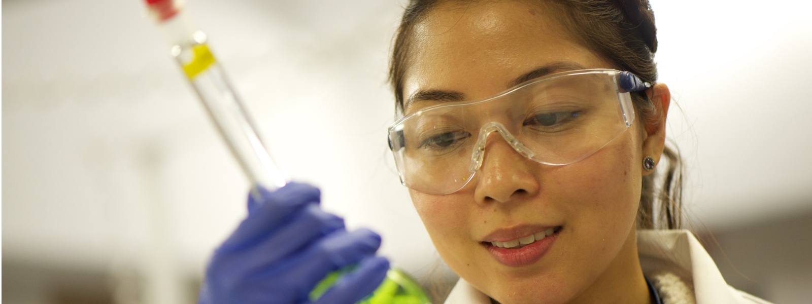 Laboratory Researcher Looking At Flask of Green Liquid 1600x600