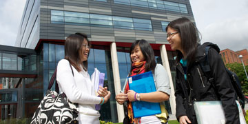 Three Student Girls Laughing Carrying Folders 360x180