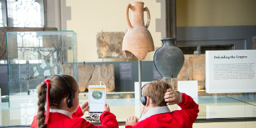 Two children looking at an tablet, learning about the Romans