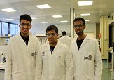 3 students wearing lab coats.