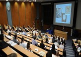 A lecture theatre filled with people attending a conference.