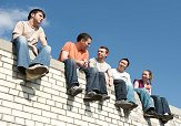 Five students sitting on a wall.