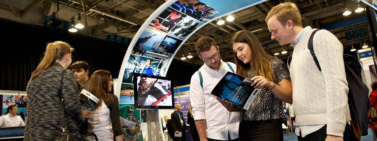 three students looking at a brochure in the middle of the Scottish Careers Fair