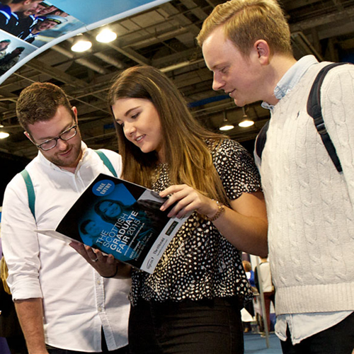 Students looking at brochure at Scottish Graduate Fair